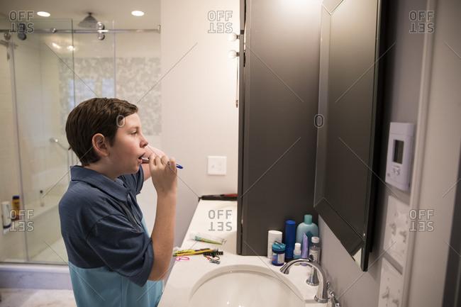 Teen Boy Looks in Mirror While Brushing His Teeth in Modern Bathroom