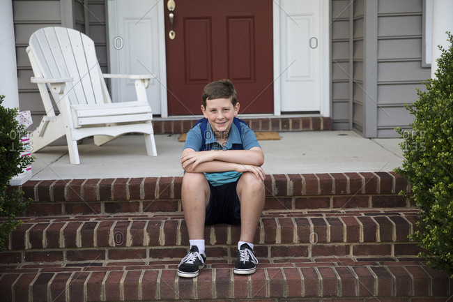 Smiling Tween Boy With Braces Sits on Brick Front Steps