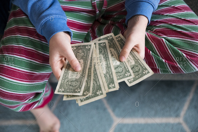 Close Overhead View of Teen Boy in Striped Pajamas Holding Money