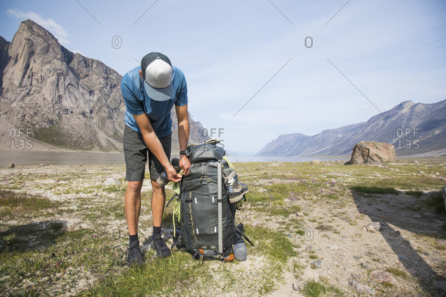 Hiker leans over to zip up backpack his large, heavy backpack.