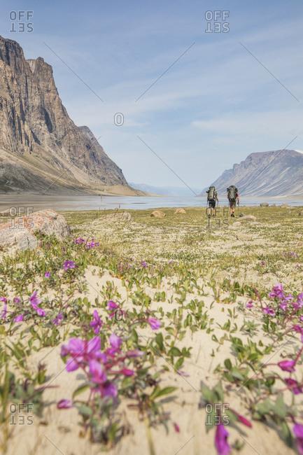 Two men explore Akshayak Pass during mountaineering trip.