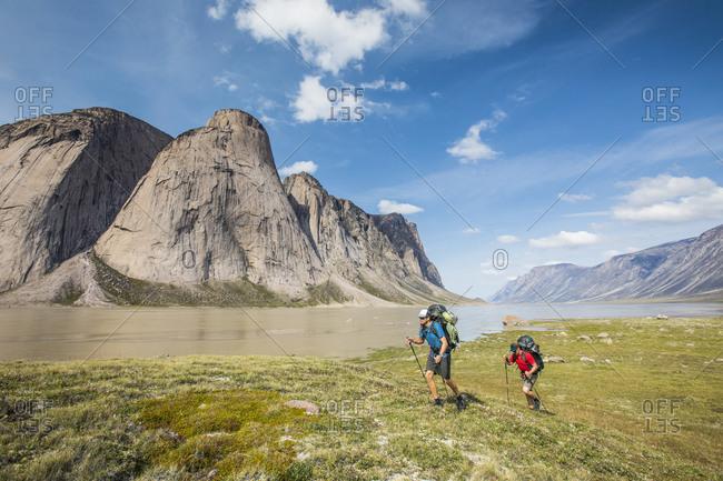 Backpackers hike over arctic tundra in Akshayak Pass