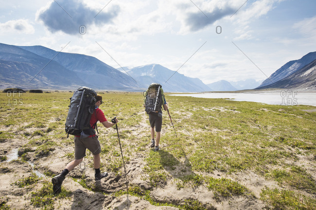 Rear view of Backpackers hike over arctic tundra in Akshayak Pass