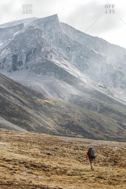 Backpacker hiking below massive granite peak in Akshayak Pass