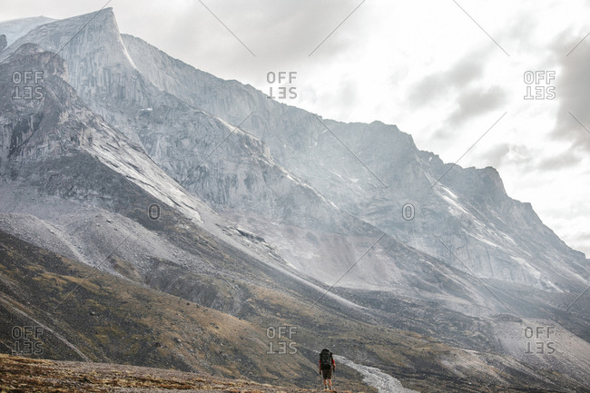 Backpacker is dwarf below massive granite mountain on Baffin Island.