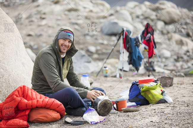 Portrait of climber sitting down for a meal at camp.