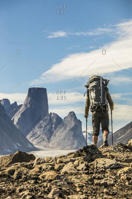 Backpacker hiking over high mountain ridge, Akshayak Pass