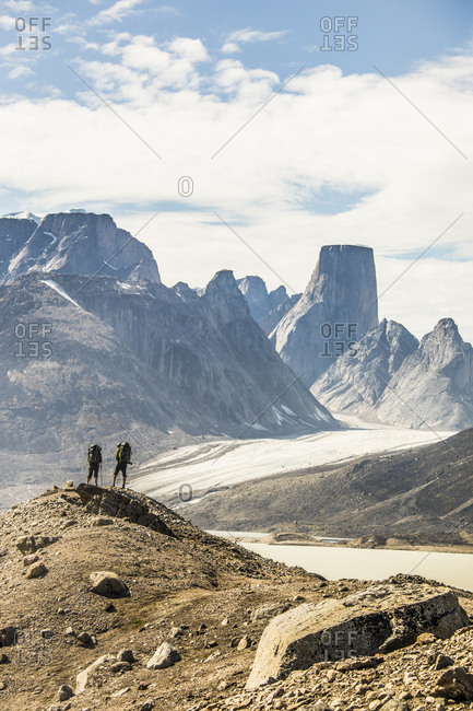 Rear view of backpackers looking at dramatic mountain view from summit