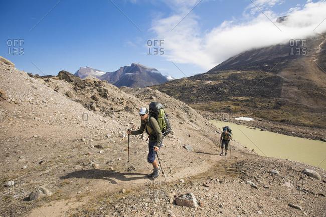 Backpackers hike up a mountain ridge in Akshayak Pass, Baffin Island.
