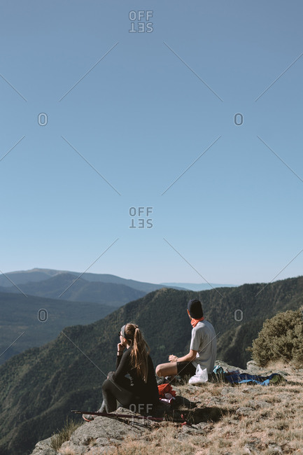 Girl and boy in the mountains watching the scenery while resting