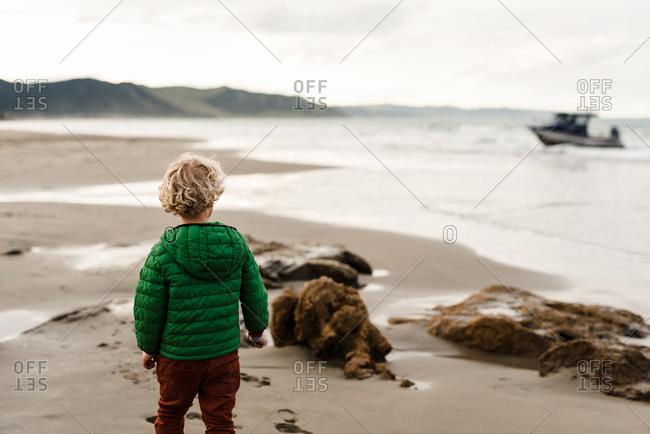 Preschooler watching boat at beach in New Zealand