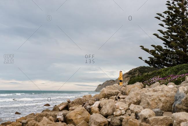 Tween in yellow coat looking at ocean in New Zealand