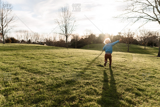 Young child frolicking in field of green grass