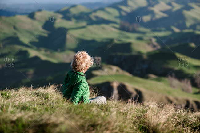Blond curly haired child looking at view of green hills