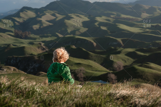 Young child overlooking green mountains in New Zealand