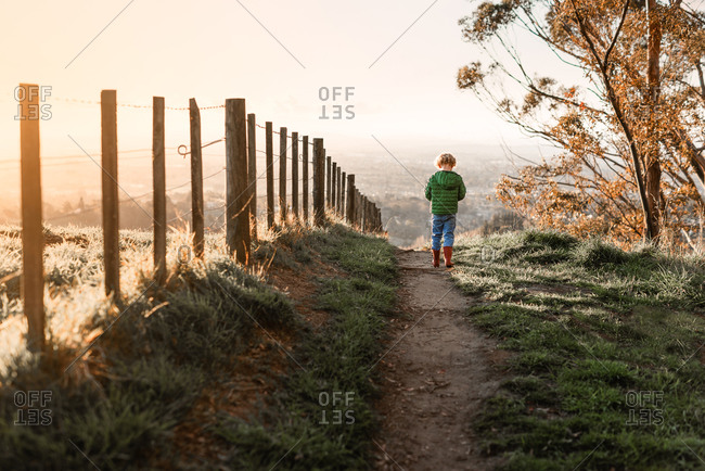 Child walking on path near fence at dusk in New Zealand