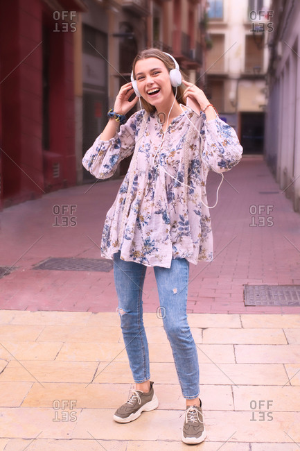 Pretty young girl listens to music with headphones and dances in and alley