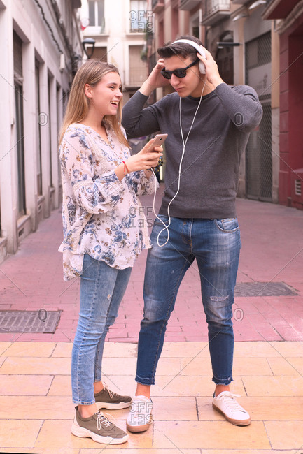 Attractive young couple listen music with headphones in the alley
