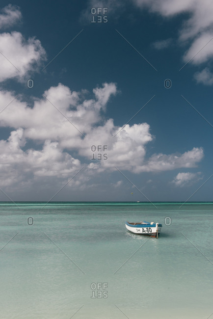Oranjestad, Aruba - February 11, 2019: A lone row boat anchored in the blue Caribbean waters off Aruba