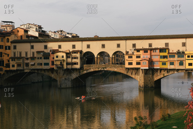Florence, Tuscany, Italy - November 30, 2018: The Ponte Vecchio as seen from the Uffizi gallery as rowers cross under
