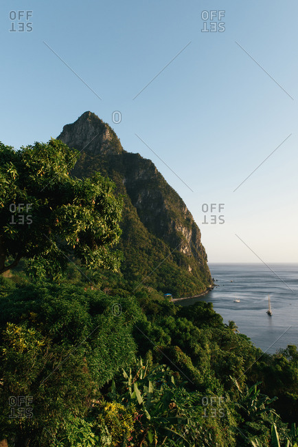 Petit Piton and the tropical coast line rise from the sea on St Lucia