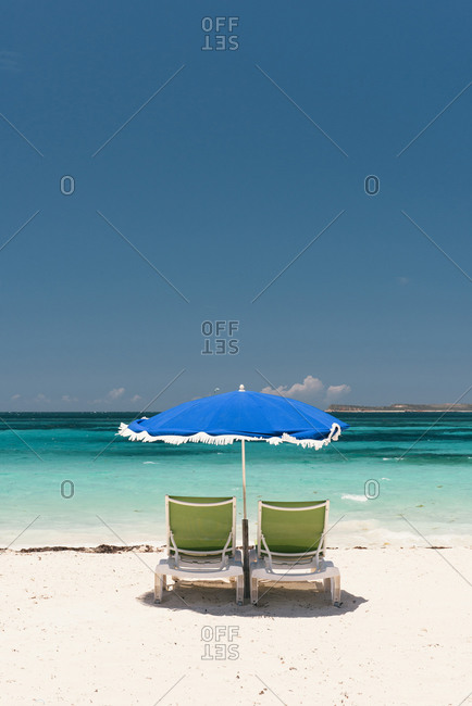 Two beach chairs and umbrella ready for tourists on the beach