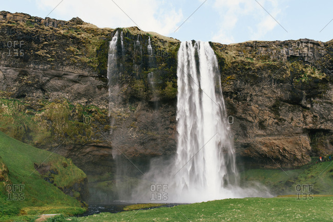 Skogafoss waterfall in Iceland cascading down on the green terrain