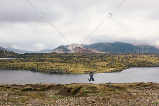 Young woman jumping for joy at scenic Iceland vista with mountains