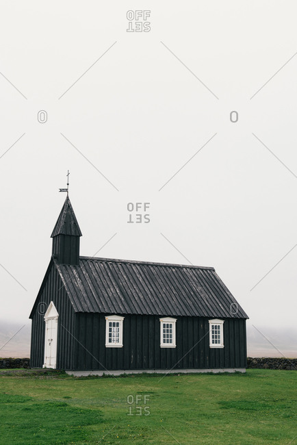 Budir Church stands alone on a foggy day in Iceland