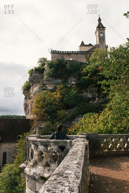Adult woman tourists looks at the medieval chateau of Rocamadour