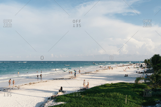 Tulum, Q.R., Mexico - July 2, 2016: Tourists walking along the white sand beach of Playa Paraiso in Tulum