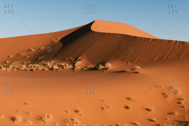 A solitary dune rising in the Sahara desert near Merzouga