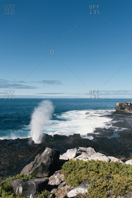 A water spout and waves crash into the volcanic shore of Espanola