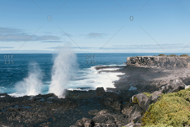 A water spout crashes into the volcanic rock of the island of Espanola