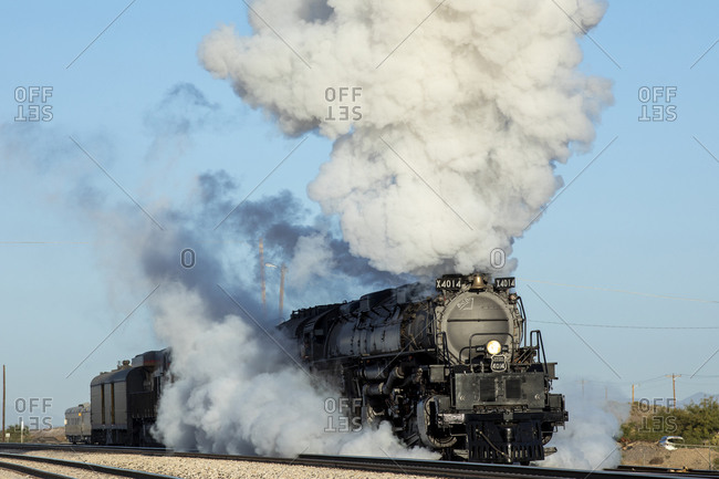 Lordsburg, NM, United States - October 20, 2019: Union Pacific steam engine 4014 smokes a lot starting to move daylight