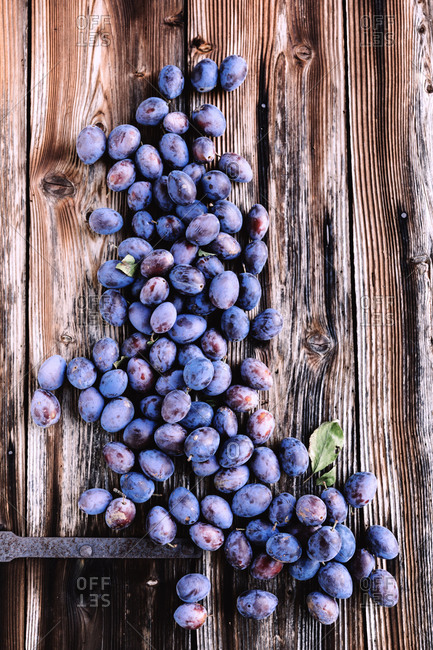 Ripe plums scattered over the wooden background.