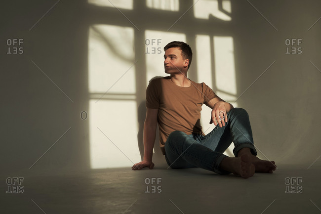 Handsome young man in t-shirt and jeans sitting on the floor