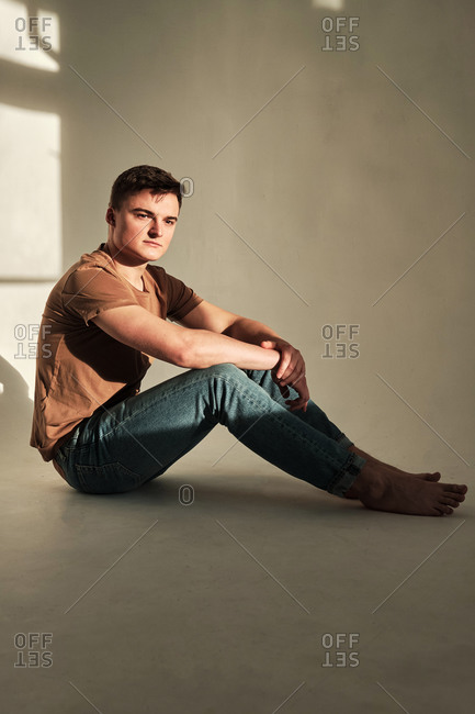 Handsome young man in t-shirt and jeans sitting alone