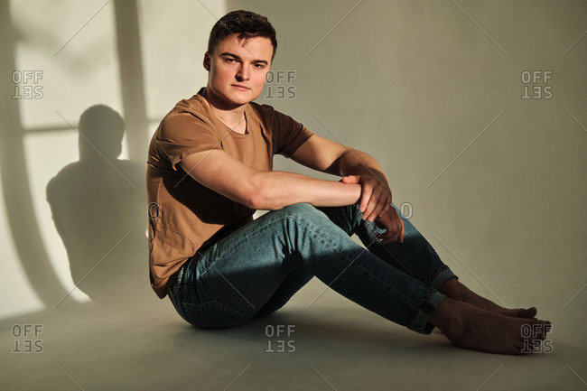 Handsome young man in t-shirt and jeans, sitting on the floor