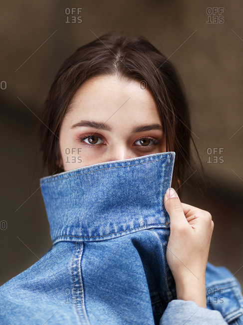 Girl with beautiful brown eyes covers her face with a denim collar