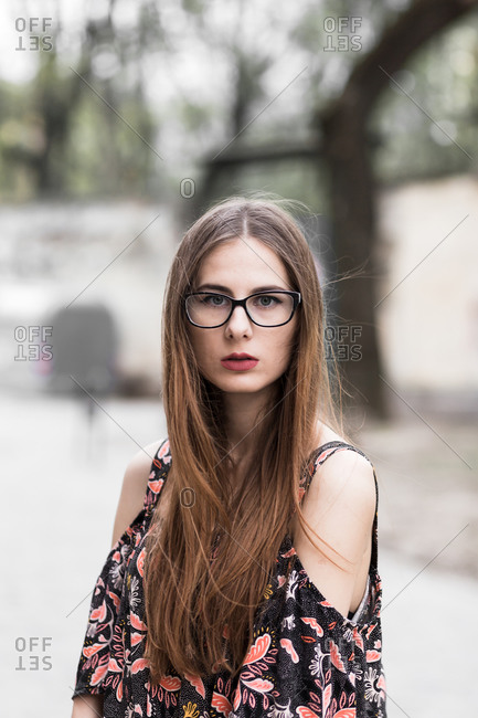 Young brown-haired millennial with glasses and light dress