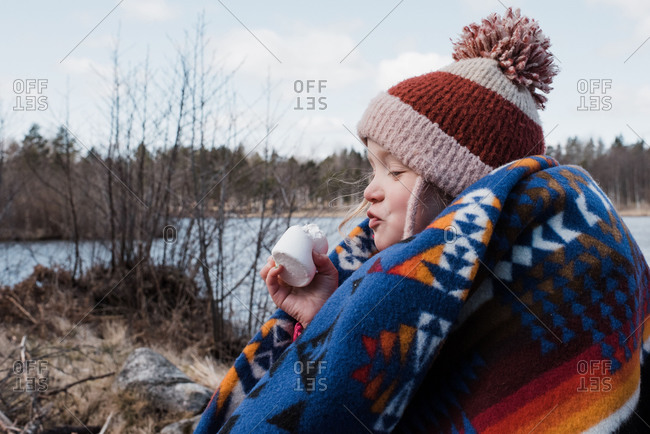 Young girl wrapped in a blanket eating a marshmallow while camping