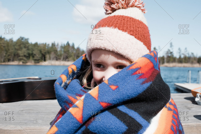Young girl wrapped up in a blanket by the lake keeping warm