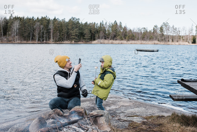 Man taking a picture of his son whilst camping eating marshmallows