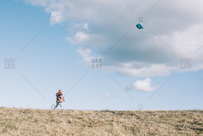 Girl flying a kite at the top of a hill with a fluffy cloud sky