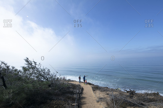 A family with small child look at the Pacific Ocean on an overlook