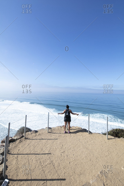 A lady with backpack looks at the ocean during a hike in San Diego