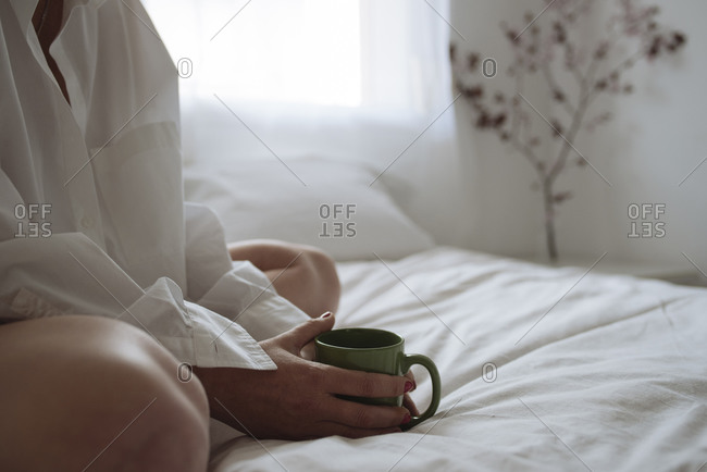 Close up of women's hands holding a cup of coffee on the bed.