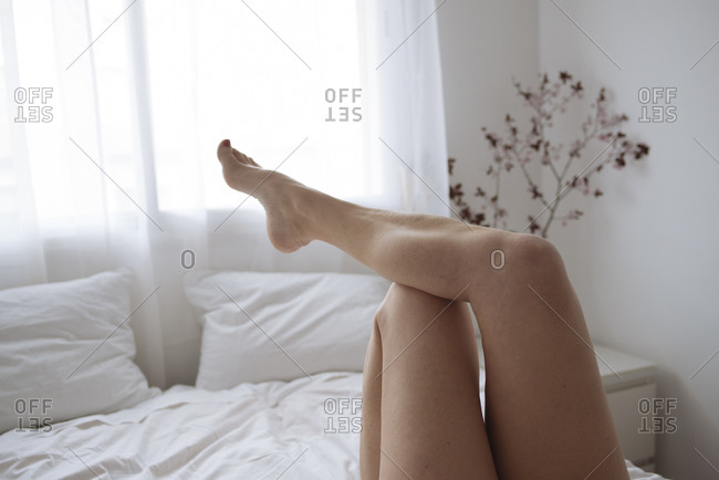 Close up of women's legs lying on bed in white bedroom.