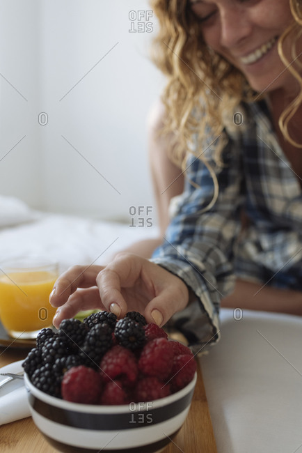 Close up of woman's hand taking a berry of a breakfast tray on the bed
